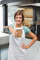 Pretty barista smiling at camera holding disposable cup at the coffee shop - PhotoDune Item for Sale
