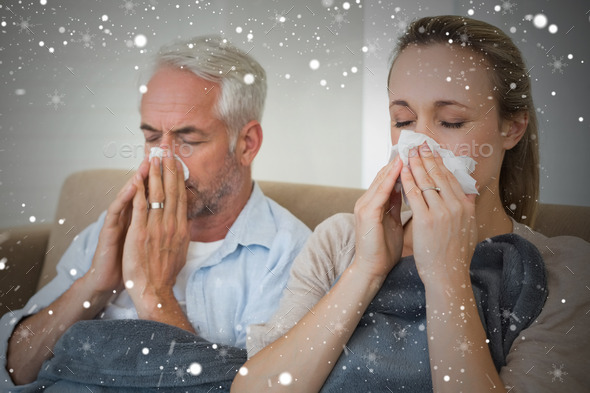 Composite image of sick couple blowing their noses sitting on the couch against snow - Stock Photo - Images