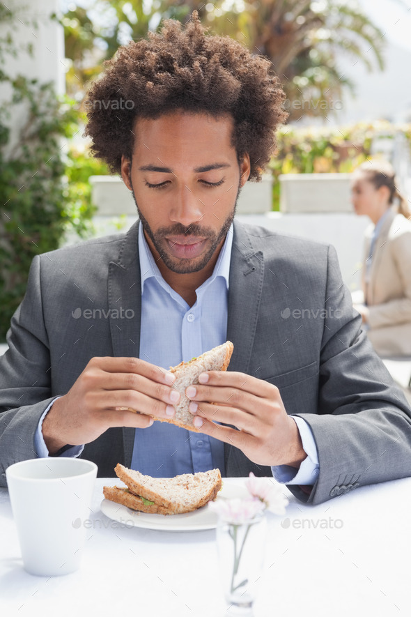 Businessman having sandwich for lunch outside at the coffee shop - Stock Photo - Images