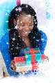 Smiling woman holding a present sitting on the floor against snow falling