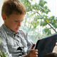 Boy Sitting By A Window Using His Tablet 1 - VideoHive Item for Sale