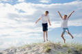 Boys jumping of a sand dune at the beach - PhotoDune Item for Sale