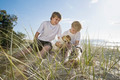 Brothers playing with dog at the beach - PhotoDune Item for Sale