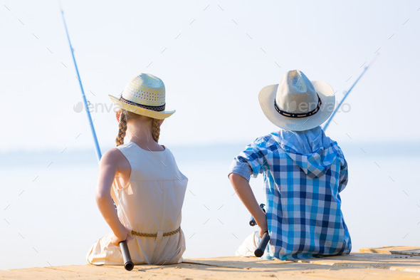Boy and girl with fishing rods - Stock Photo - Images