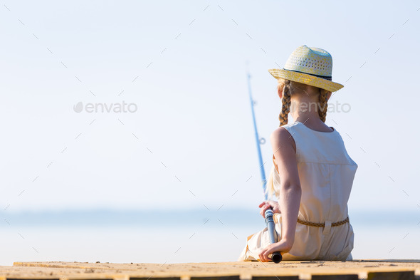 Girl in a dress and a hat with a fishing rod - Stock Photo - Images