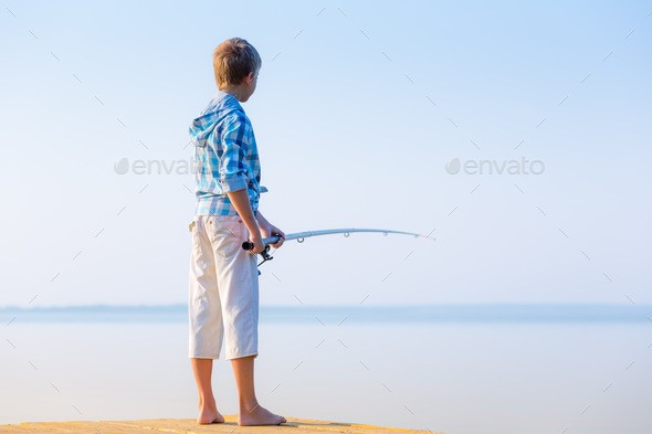 Boy in blue shirt standing on a pie - Stock Photo - Images