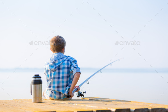 Boy in blue shirt sit on a pie - Stock Photo - Images