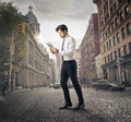 Businessman walking through the city with a tablet in his hands