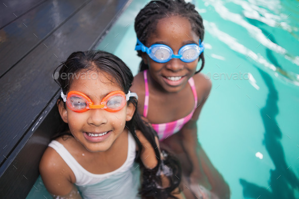 Cute little kids sitting poolside at the leisure center - Stock Photo - Images