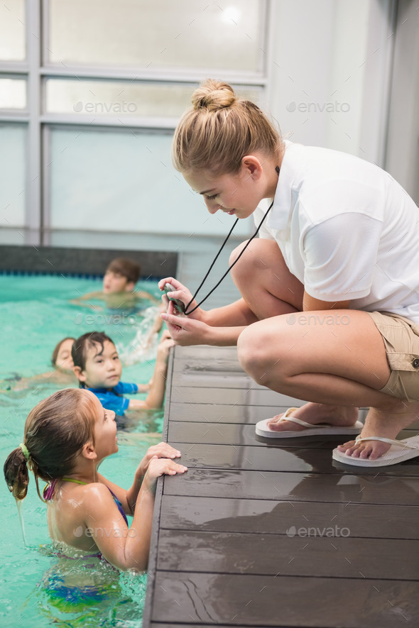 Pretty swimming coach showing boy his time at the leisure center - Stock Photo - Images