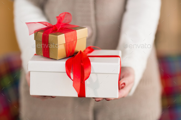 Woman with nail varnish holding gifts at home in the living room - Stock Photo - Images
