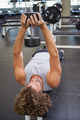 Young muscular man exercising with dumbbell in the gym - PhotoDune Item for Sale