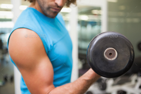 Close up mid section of man exercising with dumbbell in the gym - Stock Photo - Images