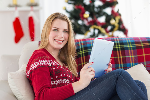 Pretty girl lying on sofa using her tablet smiling at camera at home in the living room - Stock Photo - Images