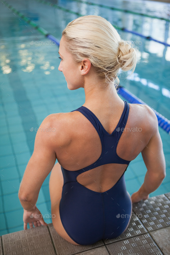 Rear view of a fit female swimmer sitting by the pool at leisure center - Stock Photo - Images