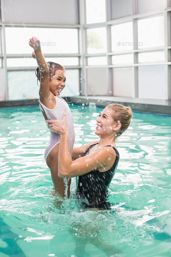 Cute little girl learning to swim with coach at the leisure center - Stock Photo - Images