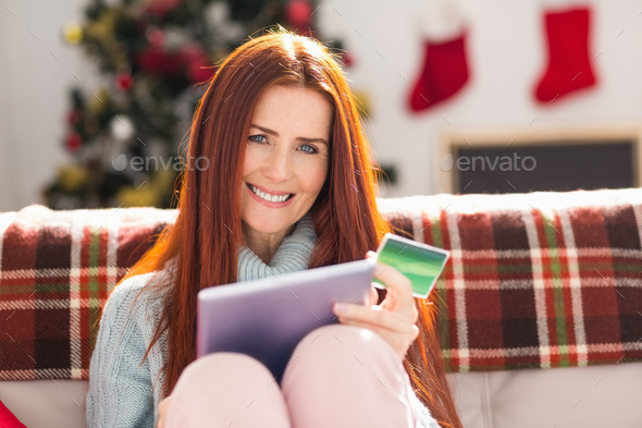 Festive redhead shopping online with tablet at home in the living room - Stock Photo - Images