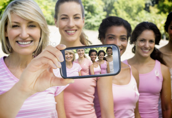 Composite image of hand holding smartphone showing photograph of breast cancer activists - Stock Photo - Images