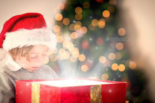 Child opening his christmas present against snow - Stock Photo - Images