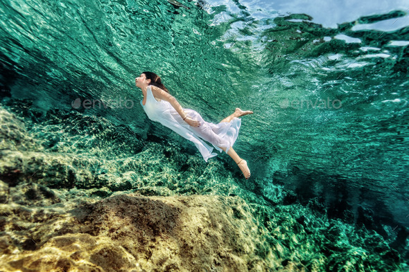 Woman swimming near rock - Stock Photo - Images