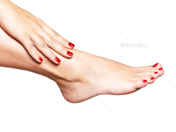 Closeup photo of a female feet with beautiful red pedicure - Stock Photo - Images