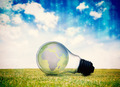 Lines of blue blurred letters falling against earth inside light bulb - PhotoDune Item for Sale