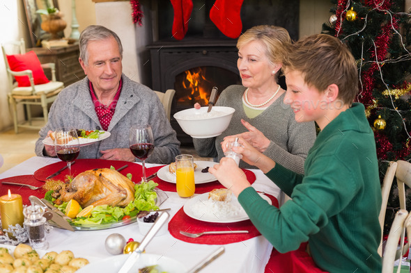 Smiling extended family at the christmas dinner table at home in the living room - Stock Photo - Images