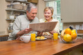 Senior couple having breakfast together at home in the kitchen - PhotoDune Item for Sale