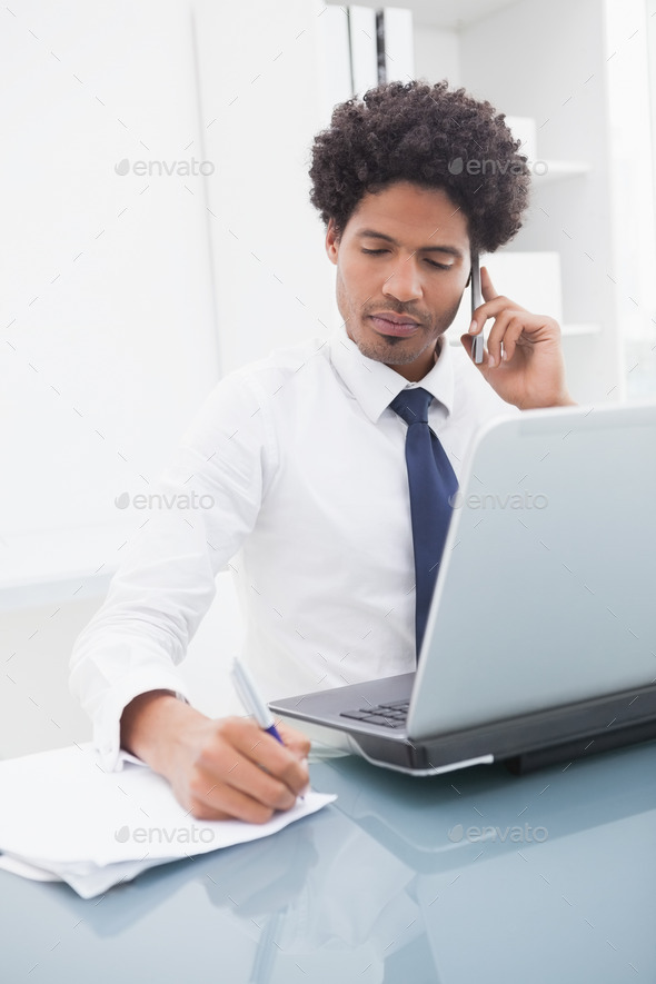 Serious businessman phoning and taking notes in the office - Stock Photo - Images