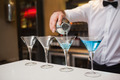 Bartender pouring blue alcohol into cocktail glass in a bar - PhotoDune Item for Sale