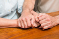 Senior couple holding hands on table at home in the kitchen - PhotoDune Item for Sale
