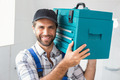 Plumber holding toolbox on shoulder in the bathroom - PhotoDune Item for Sale
