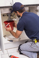 Plumber fixing under the sink in the kitchen - PhotoDune Item for Sale