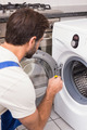 Handyman fixing a washing machine in the kitchen - PhotoDune Item for Sale