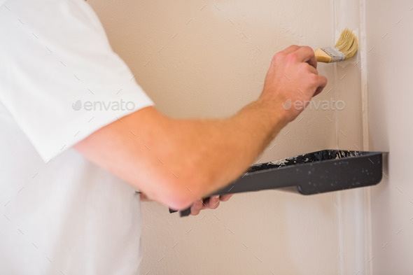 Painter painting the walls white in a new house - Stock Photo - Images