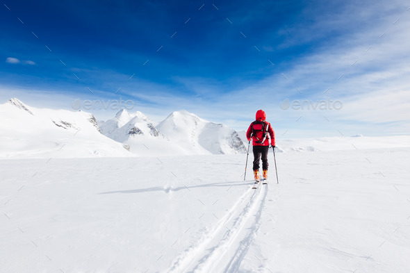 Mountaineer walking on a glacier during a high-altitude winter expedition in the european Alps. - Stock Photo - Images