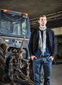 Fashion shot: handsome young man wearing jeans and coat against the tractor - PhotoDune Item for Sale