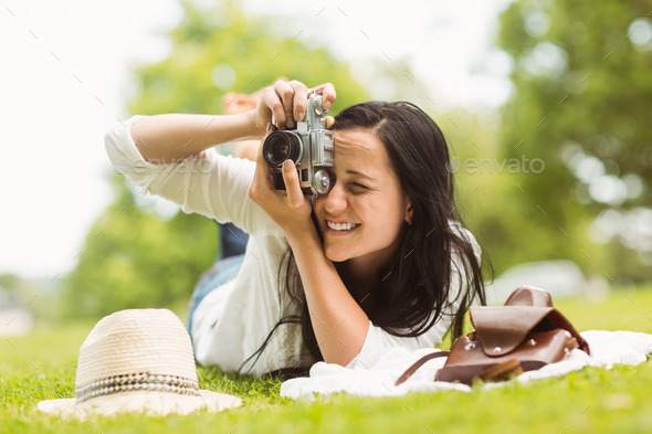 Happy brunette lying on grass taking picture in the park - Stock Photo - Images