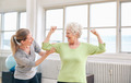 Proud elderly woman flexing her bicep with personal trainer - PhotoDune Item for Sale