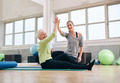 Senior woman giving high-five to her personal trainer - PhotoDune Item for Sale