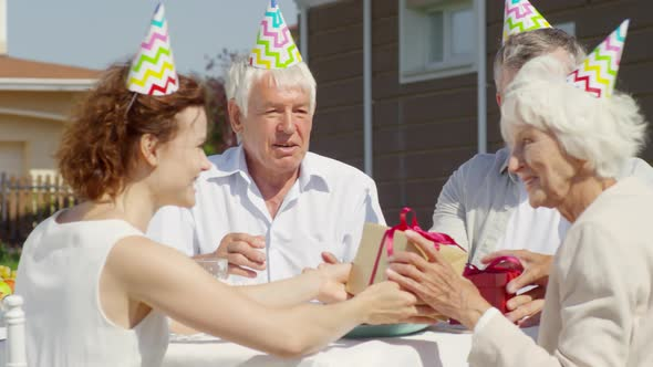 Family Giving Presents and Applauding Grandmother on Birthday Party