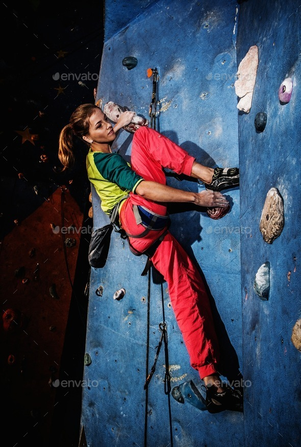 Young woman practicing rock-climbing on a rock wall indoors - Stock Photo - Images