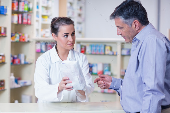 Trainee giving a bag of pills to a customer in a drugstore - Stock Photo - Images
