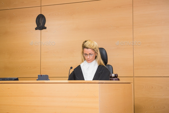 Stern judge sitting and listening in the court room - Stock Photo - Images