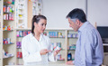 Trainee and her customer talking about medication in the pharmacy