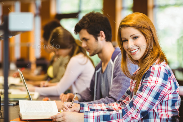 Student looking at camera while studying with classmates in library - Stock Photo - Images