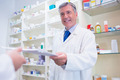 Pharmacist handing a prescription to somebody in the pharmacy