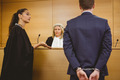 Lawyer talking with the criminal in handcuffs in the court room - PhotoDune Item for Sale
