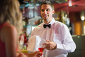 Handsome barman chatting to customer in a bar - PhotoDune Item for Sale