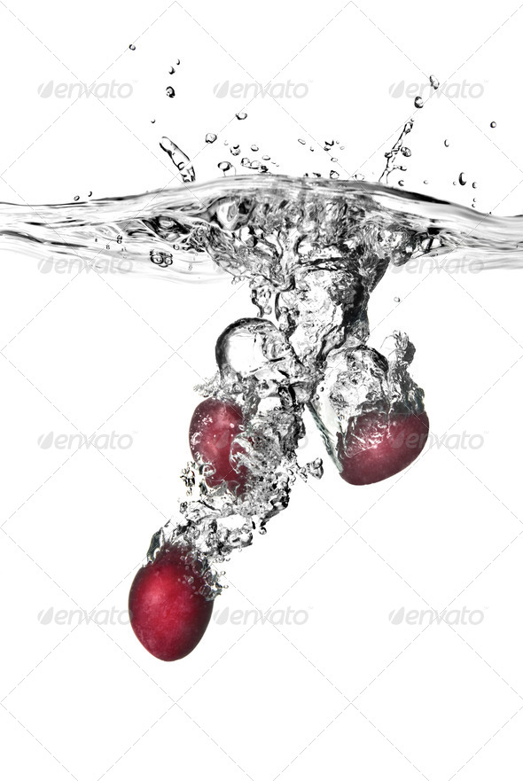 plum dropped into water with bubbles isolated on white - Stock Photo - Images